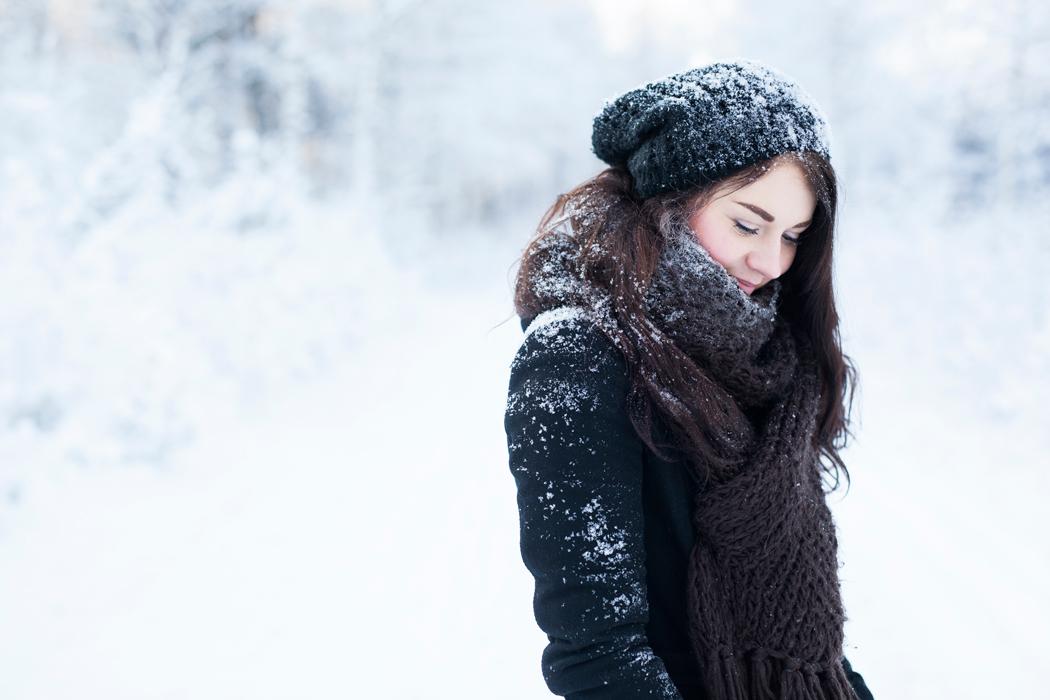 Frau mit langen Haaren in verschneiter Winterlandschaft